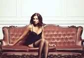Beautiful, Voluptuous And Seductive Woman Posing In Erotic Lingerie And Stockings On A Red Sofa In V poster