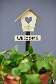 Welcome Home Sign On Blue Plan Background. Pretty Wooden Bird House poster
