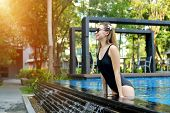 Young Female Relax In Swimming Pool, Enjoy Weather In Tropical Country On Background Of Apartment Bu poster