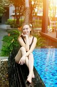 Young Woman Relax Near Swimming Pool, Enjoy Weather In Tropical Country On Background Of Apartment B poster