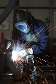 Welder Welding A Metal Part In An Industrial Environment