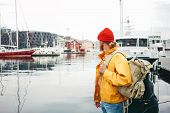 Man Tourist With Touristic Rucksack Wearing Yellow Jacket Walking Among Authentic Fishing Boats. Hip poster