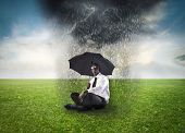 African businessman sitting under an umbrella on a green meadow with stormy cloud over him