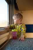 A Bright, Cute Three-year-old Boy Riding A Train Looks Out The Window, Behind Which A Dull Landscape poster