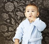 portrait of an adorable infant with his finger in his mouth wearing a bathrobe against a vintage background
