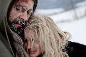 Close-up of freezing homeless couple struggle and hug