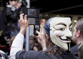NEW YORK - MAY 1: A protester wearing a Guy Fawkes mask records the march to Union Square from Bryan