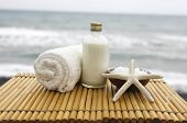 Zen concept -Stones and massage oil with salt in wooden bowl, towel on sunset