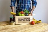 Food Donation Concept. A Man Holding A Donation Box With Vegetables, Fruits And Other Food For Donat poster