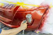 Spray Gun With Paint For Painting A Car ,man With Protective Clothes And Mask Painting Car Using Spr poster