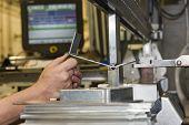 Worker Operating Metal Press Machine At Workshop. Bending Of Metal On The Machine. poster