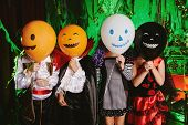 Funny children in carnival costumes with balloons on Halloween. Halloween party. poster