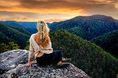 Woman Sitting On A Rock Overlooking The Valley, Mountain Gazing As The Sun Sets poster
