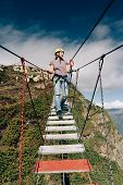 Young Happy Woman Climber Is Walking On A Rope Bridge Hanging In The Mountains Over The Precipice. A poster