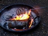 Roasting Sausages Over Campfire