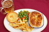A pub grub style meal of a meat pie served with mixed veg, chips, Yorkshire pudding and a glass of lager.