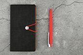 Black Notebook And Red Pen. Blank Notebook And Red Pen. Blank Notebook And Red Pen On Gray Concrete  poster