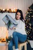 Happy Girl In Excitement Opening Christmas Box Trying To Guess What Is Inside. Excited Woman. Christ poster