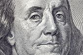 Macro close up of Ben Franklin's face on the US $100 dollar bill.