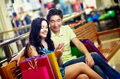 picture of tilt  - Tilt up of a happy couple using the mobile for quick and convenient communication in shopping mall - JPG