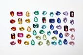 Different Beautiful Gemstones On White Background, Top View poster