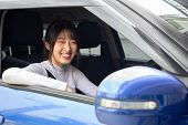 Happy Asian Women Driving A Car And Smile With Glad Positive Expression During The Drive To Work Off poster