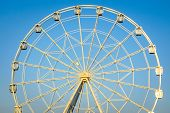 Image Of A White Ferris Wheel Against Blue Sky. Cabins Of The Ferris Wheel. poster