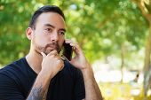 Pensive Guy Talking On Cellphone Outdoors. Handsome Man With Tattooed Arm Speaking On Mobile Phone O poster