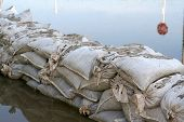 foto of sandbag  - A row of sandbags sit next to waters - JPG