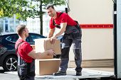 Two Young Male Movers In Uniform Carrying Cardboard Boxes From Truck poster