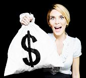 stock photo of opulence  - Euphoric business woman wide eyed with surprise and excitement holding up an unexpected windfall of a moneybag stuffed full of dollars as she pictures her newfound wealth and opulence - JPG