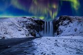 Skogafoss Waterfall In The Winter At Night Under The Northern Lights. Iceland. poster