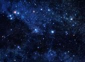 stock photo of cosmic  - Deep blue space background filled with nebulae and shining stars - JPG