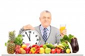 Mature man holding an orange juice with clock, fruit and vegetables on a table isolated on white bac