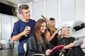stock photo of hairspray  - Male and female hairdressers setting up client - JPG