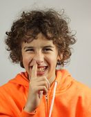 A young boy is picking his nose with a cheeky smile