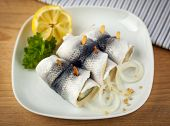 Rollmops, a german specialty with marinated herring wrapped around pickled cucumber, with mustard se