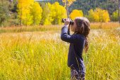 Explorer binocular looking kid girl in yellow autumn nature outdoor