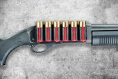 stock photo of shotgun  - A shotgun with red shell cartridge ammo isolated against a grunge gray background - JPG