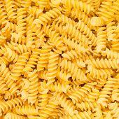 Italian Fusilli, Rotini Or Scroodle Macaroni Pasta Food Background Texture