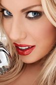 Closeup cropped headshot of a glamorous beautiful blonde vocalist or diva with shiny red lipstick si