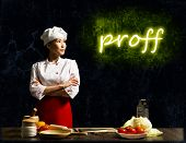Asian female chef looking at the glowing proff