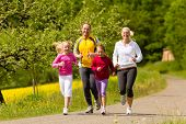stock photo of daddy  - Happy Family with two girls running or jogging for sport and better fitness in a meadow in summer - JPG