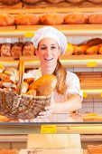 Female baker or saleswoman in her bakery with fresh pastries and bakery products