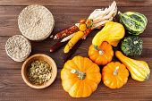 Fresh pumpkins and seeds on a wooden table
