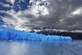 The clouds covered the sun cold. Grey glacier moves down the water of the lake. Chilean Patagonia.