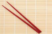 Red chopsticks over bamboo mat background.