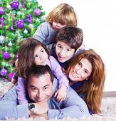 Cheerful large family having fun at home near Christmas tree, winter holidays, New Year celebration, parents with kids enjoying Christmastime