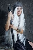 stock photo of paladin  - Girl with long white hair in chain mail and sword - JPG