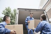 stock photo of movers  - Movers unloading a moving van and passing a cardboard box - JPG